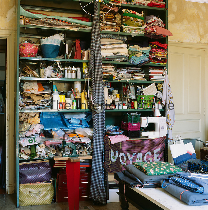 Myriam Balay Devidal's studio in her apartment in Nimes. A free-standing shelving unit is full of fabrics and haberdashery