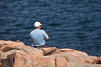 A man looks at the ocean as he sits on the rocky shore of  Acadia National Park on Mount Desert Island in Maine Wednesday June 19, 2013. Created as Lafayette National Park in 1919 and renamed Acadia in 1929, the  park includes mountains, an ocean shoreline, woodlands, and lakes.