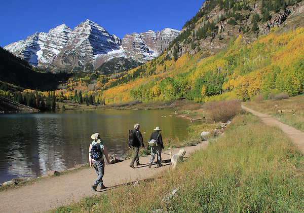 Senior couple hike with dog along Maroon Lake, Maroon Bells, Colorado. .  John offers private photo tours in Denver, Boulder and throughout Colorado. Year-round.