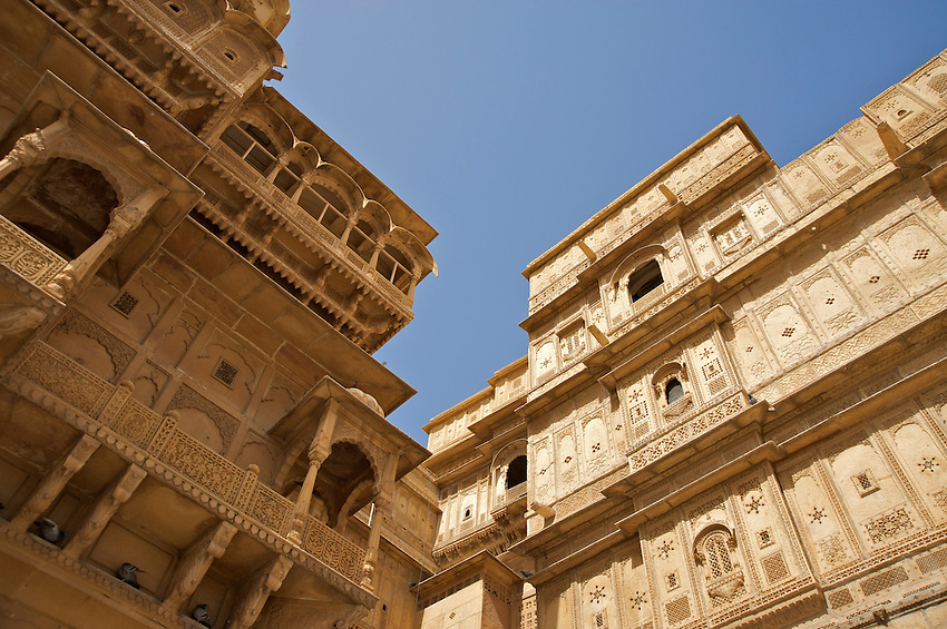 """Jaisalmer the old City and fort.Jaisalmer Fort is one of the largest of desert forts of the world. It is situated in Jaisalmer city in Indian state of Rajasthan. It was built in 1156 AD by the Bhati Rajput ruler Rawal Jaisal, from where it derives it name. The fort stands proudly admist the golden stretches of the great Thar Desert, on Trikuta Hill and had been the scene of many battles. Its massive yellow sandstone walls are a tawny lion color during the day, turning to a magical honey-gold as the sun sets and camouflages the fort making it appear a part of the picturesque yellow desert. Thus, it is also known as the """"Golden Fort"""".."""