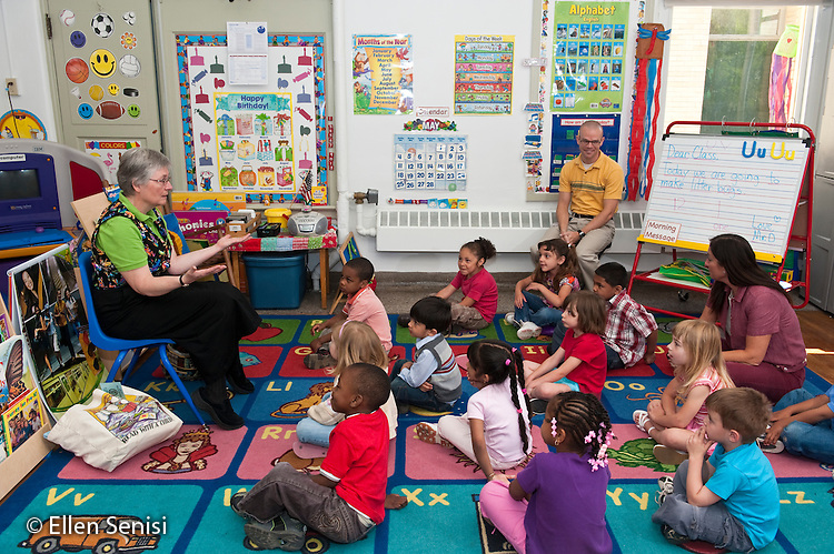 MR / Schenectady, New York. Fulton Early Childhood Education Center (urban public school early childhood education center). Pre-K classroom. Librarian from city library visits classroom for special literacy lesson as part of a community outreach program. In this component of the lesson, she uses her hands while story telling. Teacher (man with yellow shirt) and aide (woman) sit and participate with class group. ID: AI-gPd. MR: Del17, Gif1, Mos6 ©Ellen B. Senisi