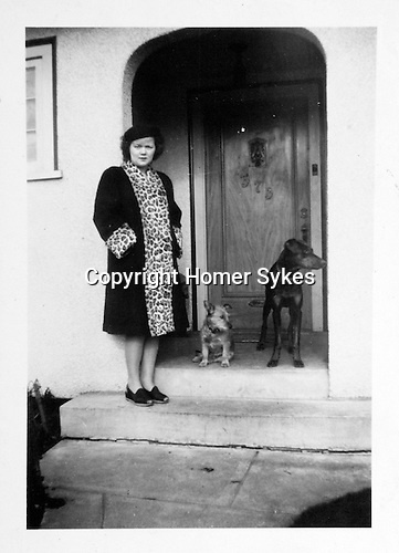 """Helen Elsie Grimmitt ( HWS - my mother ) Vancouver BC with Rusty and Rex. March 1946. """" I look like Mrs 5 by 5, its really the coat though!!"""" Outside her parents house."""
