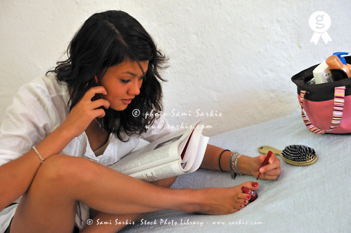 Teenager girl on phone, painting her toe nails (Licence this image exclusively with Getty: http://www.gettyimages.com/detail/91875428 )