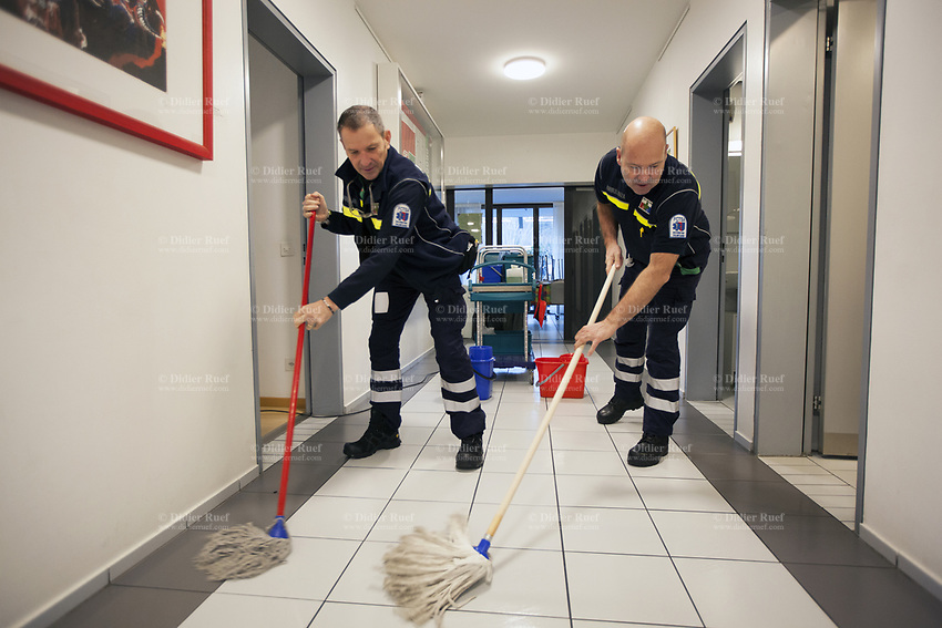 Switzerland. Canton Ticino. Pregassona. Headquarters of Croce Verde Lugano. Two paramedics are cleaning the corridor with mop on a Sunday morning. The reason is to make the environment sanitary and to remove allergens, in particular dust, stains, dirt and litter. Both men work for the Croce Verde Lugano and wear blue uniforms. Both are volunteers specifically trained in emergency rescue. The Croce Verde Lugano is a private organization which ensure health safety by addressing different emergencies services and rescue services. Volunteering is generally considered an altruistic activity where an individual provides services for no financial or social gain to benefit another person, group or organization. Volunteering is also renowned for skill development and is often intended to promote goodness or to improve human quality of life. Pregassona is a quarter of the city of Lugano.14.01.2018 © 2018 Didier Ruef