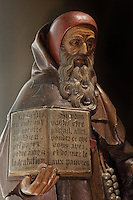 Statue of St Anthony the hermit with a book, patron saint of the Hospices and protector from epidemics and ergotism, in painted limestone, late 15th century, in Les Hospices de Beaune, or Hotel-Dieu de Beaune, a charitable almshouse and hospital for the poor, built 1443-57 by Flemish architect Jacques Wiscrer, and founded by Nicolas Rolin, chancellor of Burgundy, and his wife Guigone de Salins, in Beaune, Cote d'Or, Burgundy, France. The hospital was run by the nuns of the order of Les Soeurs Hospitalieres de Beaune, and remained a hospital until the 1970s. The building now houses the Musee de l'Histoire de la Medecine, or Museum of the History of Medicine, and is listed as a historic monument. Picture by Manuel Cohen