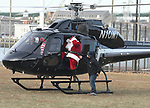 (Boston MA 12/17/17) Santa grabs his cap as the helicopter wake is apparently more severe than that produced by his sleigh and reindeer, while arriving by an executive helicopter from the North Pole to Boston's North End, Sunday, December 17, 2017, at Puopolo Park in Boston. After meeting with some children Santa was whisked off in an old fire truck to the Steriti Staking Rink for holiday music and caroling, face painting and refreshments. The event was sponsored by a number of North End businesses and organizations. Herald Photo by Jim Michaud