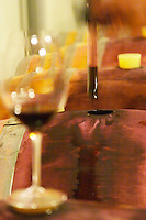 Cave P et Andre Perret in Chavannay, making Condrieu, Saint Joseph, Cote Rotie.  In the winery.  Andre Perret taking a barrel sample of red wine. A blurred glass in the foreground.  Andre André P et A Perret, Chavanay, Rhone, France, Europe
