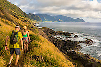 A man and woman hike the Ka'ena Point trail in the late afternoon, O'ahu.