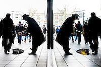 Nederland,  Rotterdam, 2 febr 2014<br /> Straatmuzikant in het centrum van de stad. Donkere man met gitaar en hoed op, gespiegeld in het glas van de etalage achter hem.<br /> Foto: Michiel Wijnbergh