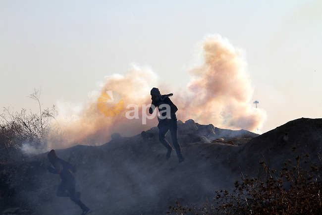 A Palestinian protester runs for cover from tear gas during clashes with Israeli security forces in the West Bank city of Tulkarm November 12, 2015. Israeli undercover forces raided a hospital in the West Bank on Thursday, shooting dead a Palestinian during an attempt to detain another man suspected of carrying out a stabbing, the Palestinian health ministry and doctors said. Photo by Nedal Eshtayah