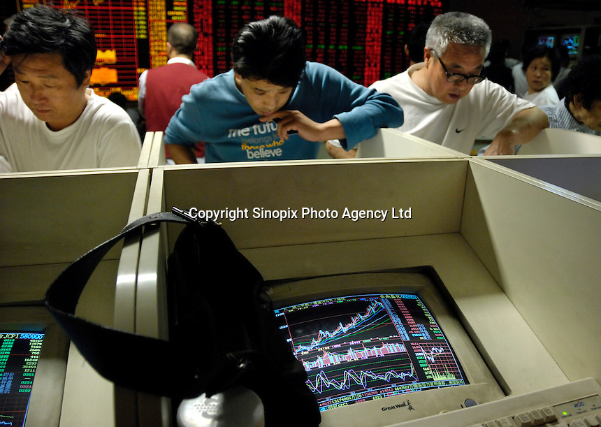 Chinese investors check stock prices on computer monitors in a stock exchange in Beijing, China. Chinese share prices broke through the psychologically important 4000-mark for the first time ever last week and dealers said the sustained Chinese advance is being driven by massive inflows of fresh funds as smaller investors take their money out of low-return bank deposits and punt on stocks..16 May 2007