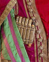 A detail of the silver-capped wooden spools on the front of one of the costumes, bound in by woven gold ribbon