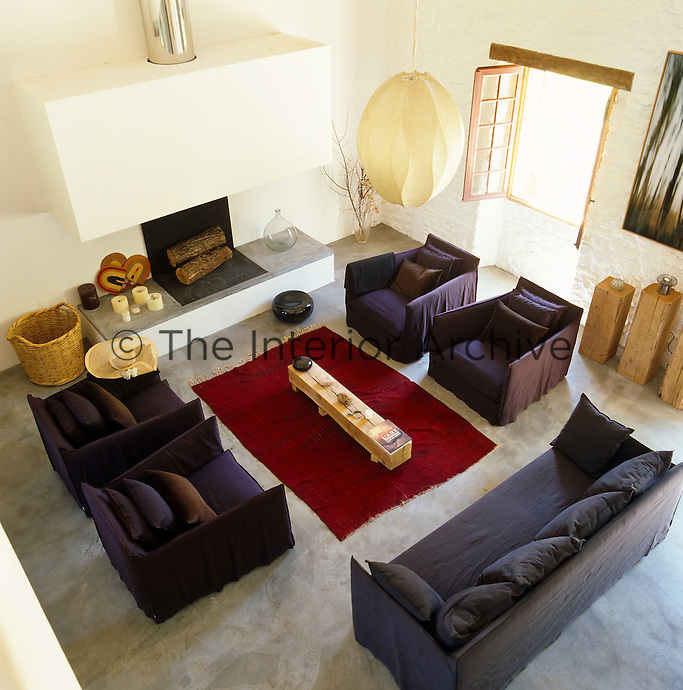 Aerial view of the living room with furniture upholstered in purple and a red rug on a polished concrete floor