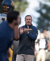 California head coach Sonny Dykes claps hands with his players during warm-ups before the game against Colorado at Folsom Field in Boulder, Colorado on November 16th, 2013.  Colorado defeated California, 41-24.