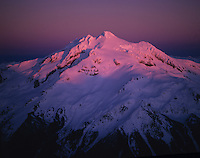 Aerial view of sunset alpenglow lighting on Glacier Peak, Glacier Peak Wilderness Area, North Cascades, Washington State.
