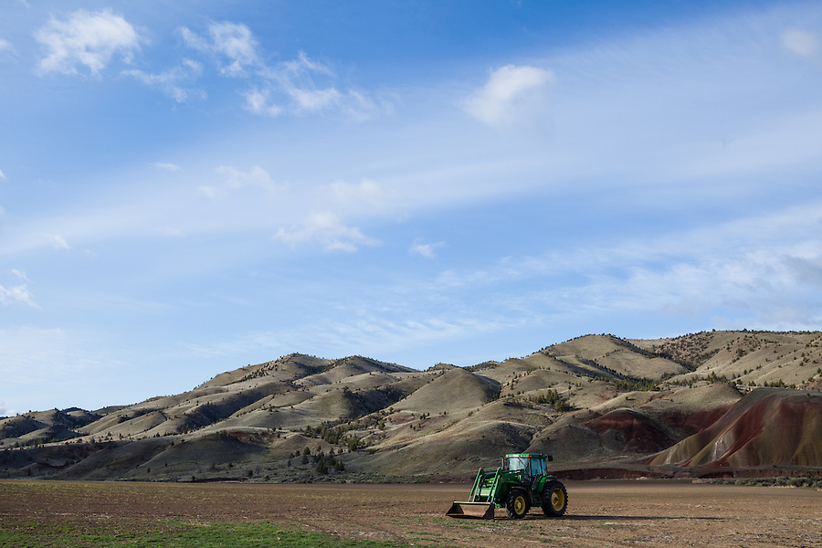 A green John Deere tractor is seen near the Painted Hills of Central Oregon, located in Wheeler County.