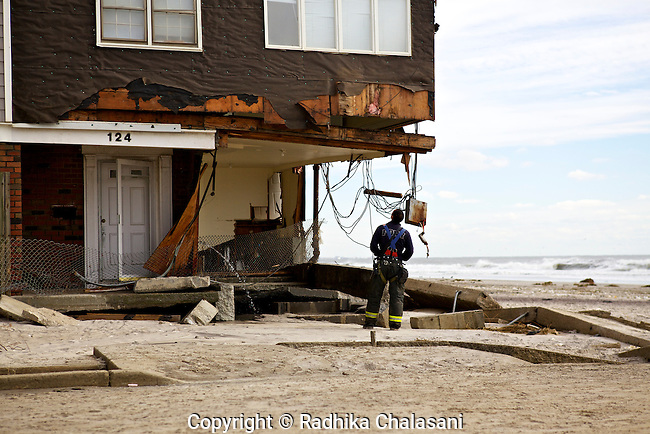 BELLE HARBOR, NEW YORK-NOVEMBER 01: A fireman checks on homes in this Rockaway, Queens neighborhood after Hurricane Sandy November 1, 2012. A large number of homes and businesses were destroyed by the storm and much of the area is without power.