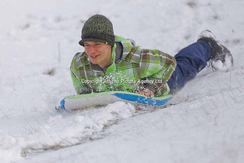 WEATHER PICTURE WALES<br /> Pictured: A young man makes the most of the snow as he sleighs down a slope on the Black Mountains near Brynamman, Wales, UK. Wednesday 23 January 2019