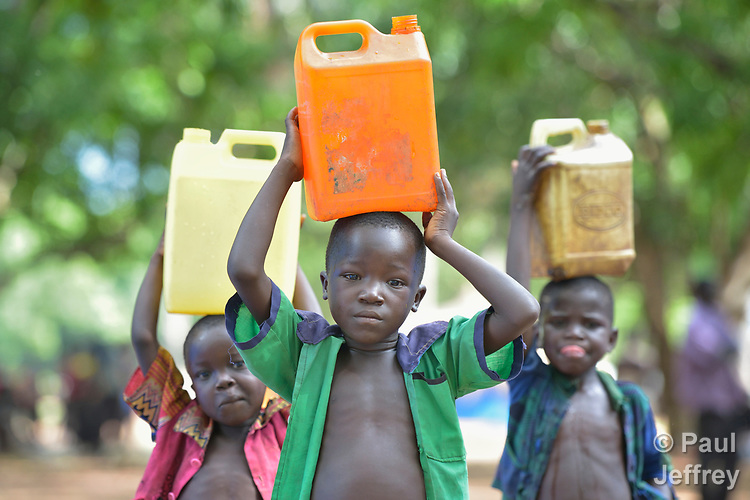 Boys carry water in a camp for more than 5,000 displaced people in Riimenze, in South Sudan's Gbudwe State, what was formerly Western Equatoria. Families here were displaced at the beginning of 2017, as fighting between government soldiers and rebels escalated.<br />