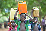 Boys carry water in a camp for more than 5,000 displaced people in Riimenze, in South Sudan's Gbudwe State, what was formerly Western Equatoria. Families here were displaced at the beginning of 2017, as fighting between government soldiers and rebels escalated.<br /> <br /> Two Catholic groups, Caritas Austria and Solidarity with South Sudan, have played key roles in assuring that the displaced families here have food, shelter and water.<br /> The camp formed around the Catholic Church in Riimenze as people fled violence in nearby villages for what they perceived as the safety offered by the church.