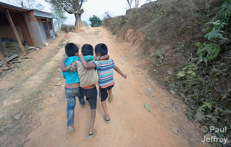 Boys walk along a road in Dhawa, a village in the Gorkha District of Nepal.
