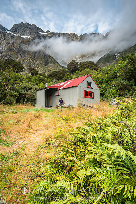 Tramper enjoying meal at Douglas Rock Hut in Copland Valley under Southern Alps, Westland National Park, West Coast, South Westland, World Heritage Area, New Zealand