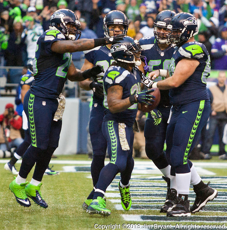 Seattle Seahawks running back Marshawn Lynch , center, celebrates a touchdown after receiving a  hovel pass from quarterback Russell Wilson for a touchdown with teammate in their game against the Minnesota Vikings  at CenturyLink Field in Seattle, Washington on  November 17, 2013.  The Seahawks beat the Vikings 41-20.  ©2013.  Jim Bryant. All Rights Reserved.