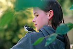 Baby bird, Violet Green Swallow, on girl's (14 years old) shoulder looking at camera in backyard, selective focus on bird and girl, Marysville, Eashington State USA  MR
