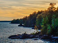 Sunset light in the sky hovers over the eastern shoreline of Madeline Island in the Apostle Island chain from Big Bay State Park, Ashland County, Wisconsin