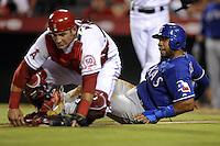 PBX04. ANAHEIM (CA, EE.UU.), 19/07/2011.- El jugador de los Rangers Elvis Andrus (d) se barre a la base junto a Jeff Mathis (i) de los Angelinos hoy, martes 19 de julio de 2011, durante el juego de la MLB en el estadio Angel de Anaheim, California (EE.UU.). EFE/PAUL BUCK.