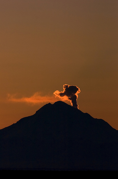 A steam plume rises at sunset from Mount Redoubt volcano, about 50 miles across Cook Inlet from Soldotna, Alaska, at the beginning of an eruptive period in 2009.