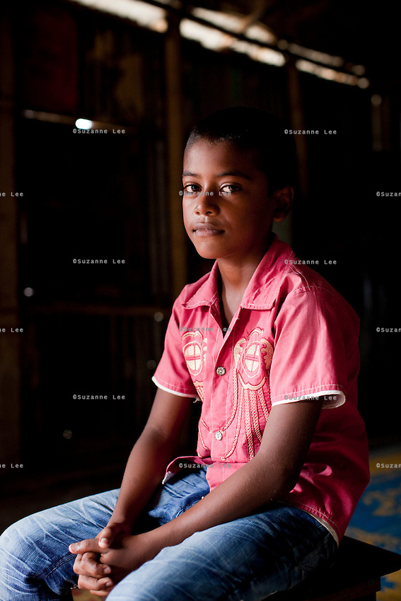 """Oli Ahmed (11) sits for a portrait in the meeting hut of a Children's Group in Bhashantek Basti (Slum) in Zon H, Dhaka, Bangladesh on 23rd September 2011. Oli says, """"We are in extreme poverty. If our parents get a good price for our marriages, there is nothing we can do. (Also,) we are now in the era of gender equality and girls should be allowed to study instead of being married off."""" Oli wants to be a doctor when he grows up. The Bhashantek Basti Childrens Group is run by children for children with the facilitation of PLAN Bangladesh and other partner NGOs. Slum children from ages 8 to 17 run the group within their own communities to protect vulnerable children from child related issues such as child marriage. Photo by Suzanne Lee for The Guardian"""