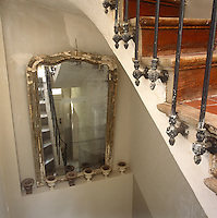A mirror with a distressed frame rests on a small shelf with miniature urns in a stair-well beside a tiled staircase.