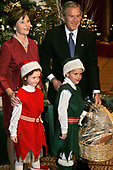 First Lady Laura Bush and United States President George W. Bush accept a basket of books from Caroline MacKinnon of Washington (L) and Andrew McSlarrow of Falls Church, VA, both 5, during the Twenty-fourth annual Christmas in Washington pageant December 11, 2005 at the National Building Museum in Washington, DC. The basket contained books as a gift for the Children's National Medical Center.  <br /> Credit: Chip Somodevilla / Pool via CNP