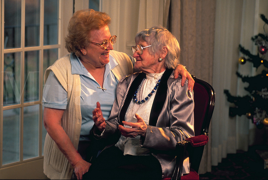 Health care worker smiling and talking with elderly woman.