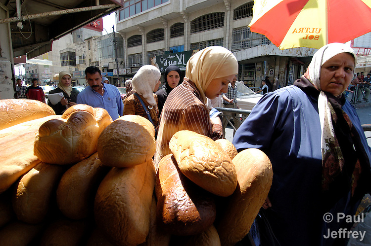 Palestinians walk past a bread shop in the West Bank city of Ramallah.