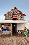 A woman sits on the porch of her coastal cottage in Nags Head, North Carolina