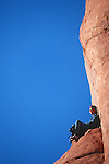 Hiker resting on a stone throne in Arches National Park