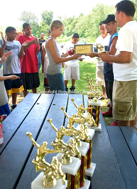 WATERBURY, CT - 05 AUGUST 2006 - 080506JW01.jpg --  Pee Wee Reese League Town Plot Yankees player Erick Kenney receives his award  and trophy from assistant coach Felix Rodriguez, coach Ken Curry , and State Rep. Anthony D'Amelio, R-71st who sponsored the event which celebrated the teams 2nd place finish in their firast tournament. Besides his trophy, Kenney received a Golden Glove award and was voted by the team as MVP.   Jonathan Wilcox Republican-American