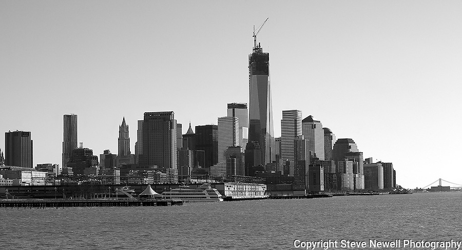 """Rebuilding Faith"" Black and White Downtown Manhattan New York. I shot this Downtown Manhattan Skyline scene while on a boat tour in the days before the worst storm in 20 years blew in lasting three days. The strong winds made it difficult to stay warm, hold my camera stable on my monopod and stay out of the water spray from the waves created by the boat. The New World Trade Center tower was just finishing construction. During the storm Governors in surrounding states and New York banned driving personal vehicles on the public highways for a couple days.  Being from Lake Tahoe I came prepared for the weather and was excited to capture New York City and Central Park with fresh snow. The incredible skyline of Manhattan was breathtaking. Growing up in California, visiting San Francisco as an adult regularly and shooting it many times as a professional photographer didn't prepare me for the magnitude of the impressive size and quantity of the buildings and skyscrapers that form the skyline of Manhattan. My hat is off to the Architects and Engineers who contributed to building the touted greatest city on Earth. Black and white photography is still my favorite so you will see many images offered in Color and BW."
