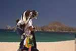 Female beach vendor walking on the beach (playa), Cabo San Lucas, Baja California, Mexico