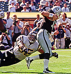 Oakland Raiders vs. San Diego Chargers at Oakland Alameda County Coliseum Sunday, October 11, 1998.  Raiders beat Chargers  7-6.  San Diego Chargers linebacker Junior Seau (55) dives for Oakland Raiders quarterback Donald Hollas (12).