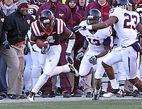 Nov 27, 2010; Charlottesville, VA, USA; Virginia Tech Hokies running back David Wilson (4) runs in front of Virginia Cavaliers cornerback Chase Minnifield (13) and Virginia Cavaliers safety Dom Joseph (23) during the game at Lane Stadium. Virginia Tech won 37-7. Mandatory Credit: Andrew Shurtleff-