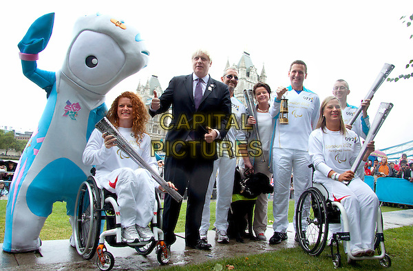 Mayor of London Boris Johnson welcomes the Paralympic flame to City Hall with Torchbearers Francesca Porcellato, Jan Wilson, William Noble, Esther Weber and Jim Muirhead ahead of the Paralympic games. London, England..August 29th 2012.full length black suit purple tie shirt wheelchair white mascot hand thumb up.CAP/AG/PP.©Amer Ghazzal/PP/Capital Pictures.