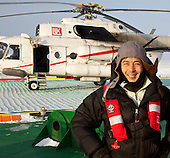 Photographer Justin Jin in front of the helicopter that brought him to the LUKoil Varandesky Oil Terminal in Arctic Russia.