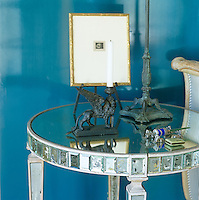 In the living room a turquoise lacquered screen creates a backdrop for a collection of figurines and a gilt-framed print on the mirror-glass surface of an inlaid side table
