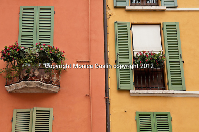 Brightly colored windows and flower covered balconies in Brescia, Italy