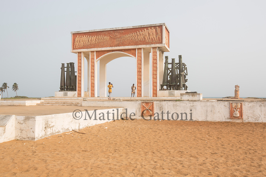 Benin - Ouidah - Two local tourists take each other photograph below the Door of No Return. Erected by UNESCO and the Government of Benin, the Door of No Return is located in Ouidah and honours the millions of African slaves who sailed from the city's shores to the New World plantations between the 17th and the 19th centuries.<br /> Ouidah is the most important historical city in Benin and also the world's capital of voodoo. The city hosts the Temple of the Pytons, where the sacred serpents have been revered by the local population for centuries.