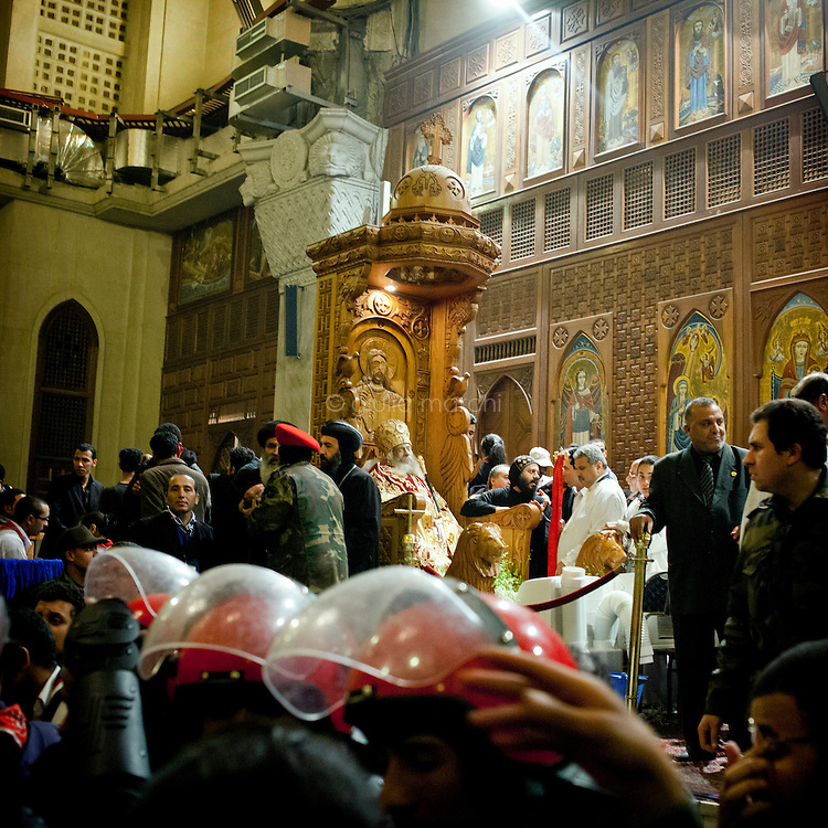 Egypt / Cairo / 18.3.2012 / Police and religious authorities around the body of Pope Shenuda III which is exhibited to the public for the first time after his death. Thousands of grieving Copts flocked to St Mark's Coptic Cathedral in Abbasseya on March 18th, for visiting Pope Shenouda III, the spiritual leader of the Middle East's largest Christian minority, died the 17th of March. Three persons have been crushed to death and 137 injured near the St Mark's Coptic Cathedral the evening of the 18th, first day of exhibition of the body of the Pope. Pope Shenuda III died at the age of 88, after a long battle with illness and based on his wishes he had been buried on March 20, at St. Bishoy monastery in Wadi Natrun in the Nile Delta where he spent his time in exile after a dispute with late president Anwar Sadat. Cairo, Egypt. March 18th, 2012.