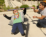 Gage Kingsland, 6, plays limbo as Adrian Barrera, 18, holds the bar during the 7th Annual Easter Fiesta at Western Nevada College Saturday, March 26, 2016. The event, hosted by the Association of Latin American Students, had 3 separate egg hunts, face painting, limbo, musical chairs, ring toss, sack races, bowling,  food, music and a piñata.  Barrera is a member of the student association. <br />